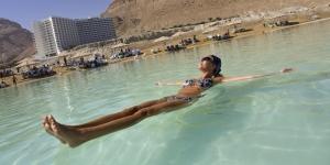 Woman floating in the Dead Sea, En Bokek, Israel, Middle East
